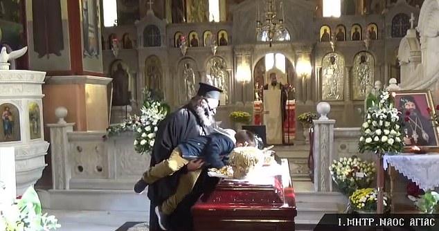 Zemërimi në Greqi pasi prifti ngre një fëmijë të puthë arkivolin e një peshkopi i cili vdiq nga COVID-19